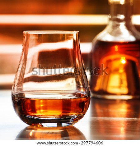 Brandy in a bottle with glass in front of modern background - stock photo