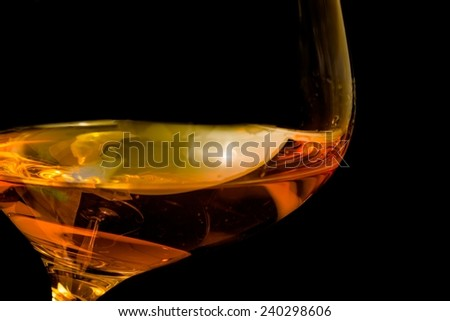 brandy in elegant glass tilted with space for text on black background - stock photo