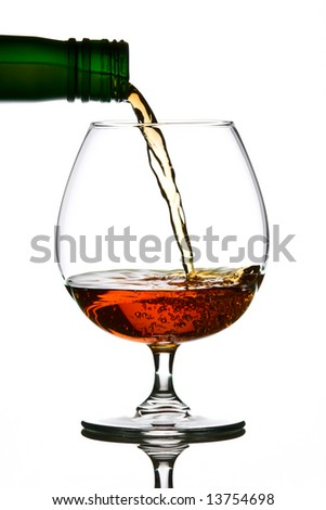 Brandy pouring from green bottle to glass - stock photo