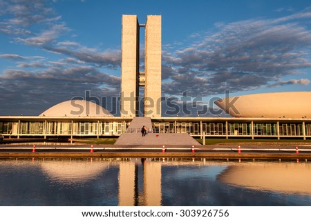 BRASILIA, BRAZIL - June 3, 2015: Brazilian National Congress reflected on water by sunset. The building was designed by Oscar Niemeyer in the modern Brazilian style. - stock photo