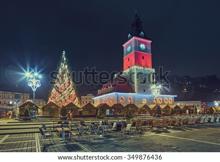 BRASOV, ROMANIA - 10 DECEMBER, 2015: Night scene in the Council Square with Christmas tree and traditional fair near the old City Hall building decorated and illuminated for Christmas holiday.
