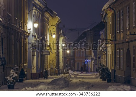 BRASOV, ROMANIA - 29 DECEMBER, 2014: Peaceful winter night urban view with snowy backstreet in the historic center of Brasov, the 7th largest city and most visited in Romania. - stock photo