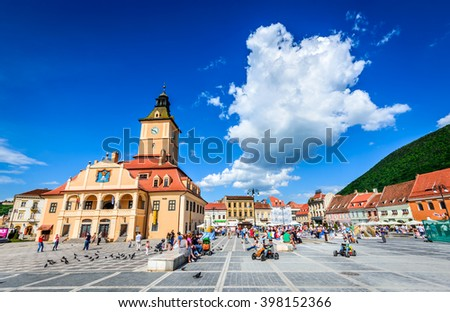 BRASOV, ROMANIA - 31 MAY 2015: Tourits walks in Main Square, landmark with Council House in medieval center of Brasov, Transylvania. - stock photo