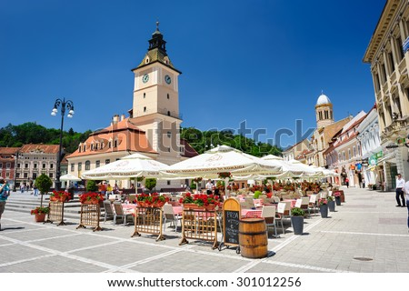 Brasov, Transylvania, Romania, 6th July 2015: Brasov Council Square is historical center of city, people walkinng and sitting at outdoor terraces and restaurants. - stock photo
