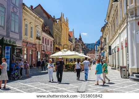 Brasov, Transylvania, Romania, 6th July 2015: Republic street is par of pedestrian area in historical center of city, people walkinng and sitting at outdoor terraces and restaurants. - stock photo