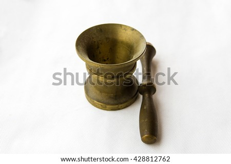 Brass ancient mortar to grind coffee on white table. Elegant classic coffee beans. Heavy metal coffee mortar.  - stock photo