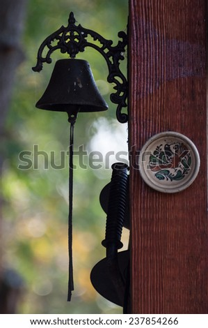 brass bell and a decorated plate - stock photo
