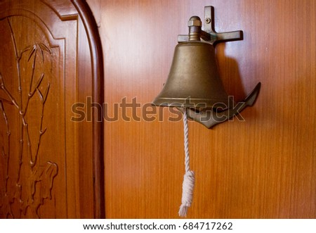 brass bell with rope on the wooden interior of a boat