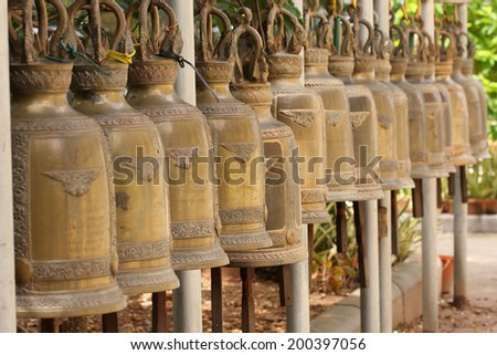 Brass bells hang in row in buddhist temple, Thailand