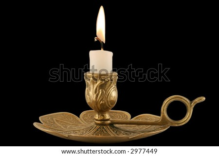Brass Candleholder - horizontal - Decorative antique brass candelabra with brightly lit white pillar candle.  Isolated over black. - stock photo