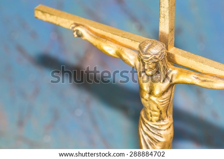 Brass  Cross with crucified Jesus Christ on blue retro background close up - stock photo
