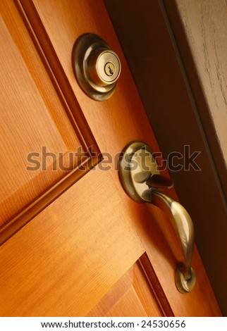 Brass door handle and deadbolt on wooden door - stock photo