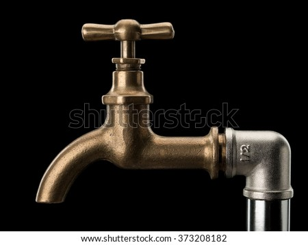 Brass faucet and a water-pipe it is isolated on black