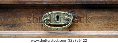 Brass handle  of the drawer of an antique furniture. - stock photo