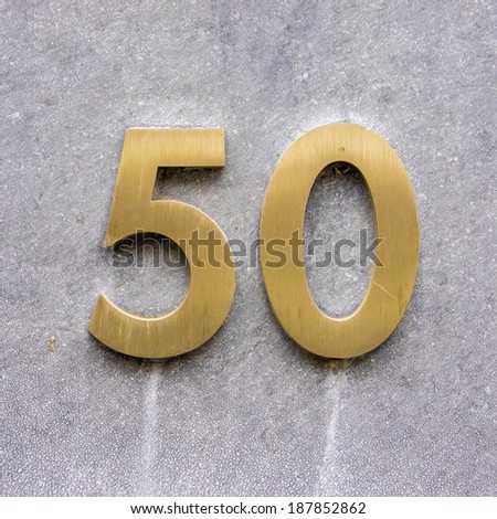 Brass house number fifty on a stone wall - stock photo