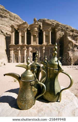 Brass jugs with Monastery of Petra on background. - stock photo