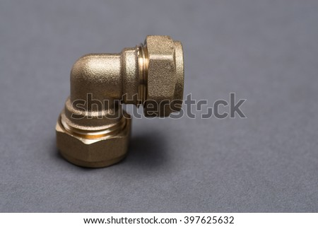 Brass plumbing compression fittings on grey surface - stock photo