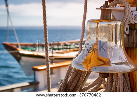 Brass ship bell on a classic sailboat at sea. Close up of the shiny bell reflecting the sails. - stock photo