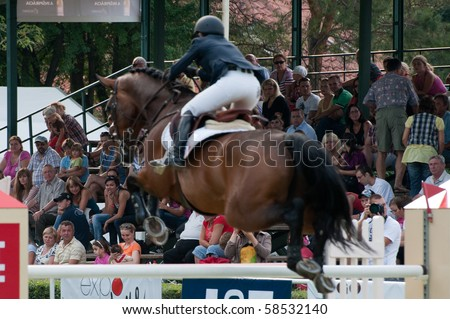 BRATISLAVA, SLOVAKIA - AUGUST 5: audience watches as one of participants jumps over hurdle  during first round of qualification to Grand Prix CSIO-W*** August 5, 2010 in Bratislava, Slovakia - stock photo