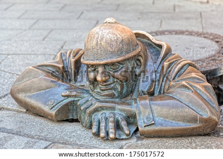 BRATISLAVA, SLOVAKIA - JULY 23,2013. Cumil - statue of man peeking out from under a manhole cover . Popular attraction was made in 1997 by sculptor Viktor Hulik.