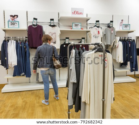 BRATISLAVA, SLOVAKIA - SEPTEMBER 25, 2017: White middle aged woman chooses clothes in s.Oliver fashion store. s.Oliver is a German fashion company headquartered in Rottendorf.