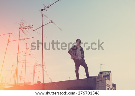 Brave and young traveler standing at sunset on high roof and looking far away (intentional sun glare and vintage color) - stock photo