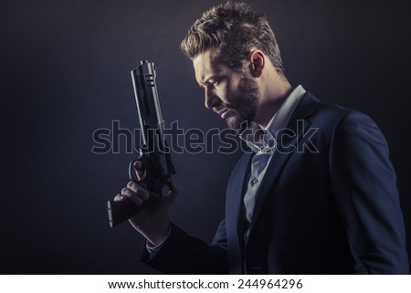 Brave cool man holding a dangerous weapon on dark background - stock photo