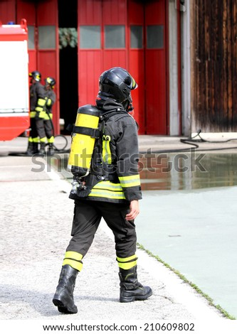 brave firefighter with oxygen tank in action 2 - stock photo