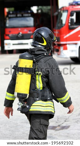 brave firefighter with yellow oxygen cylinder and the helmet walks towards the fire - stock photo