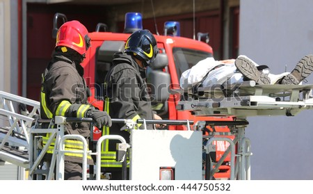 brave firefighters on the fire truck cage save the wounded person with the stretcher