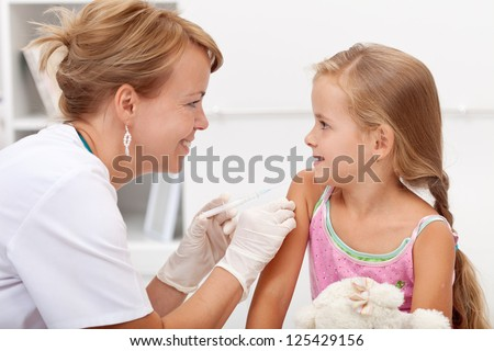 Brave little girl receiving injection or vaccine with a smile - stock photo
