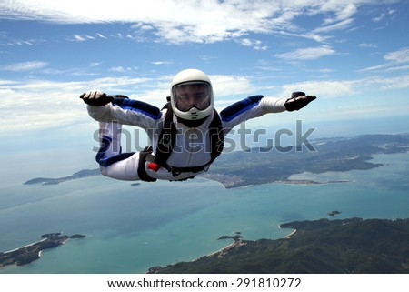 brave man practicing parachuting over the beach, sea and paradisaical islands.   - stock photo