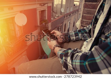 Brave man sitting on the top of the roof with mobile phone in his hand (intentional sun glare) - stock photo
