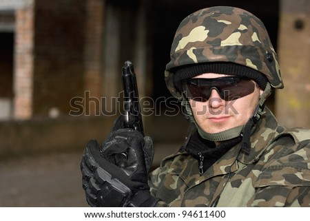 Brave man with a gun in neglected house - stock photo