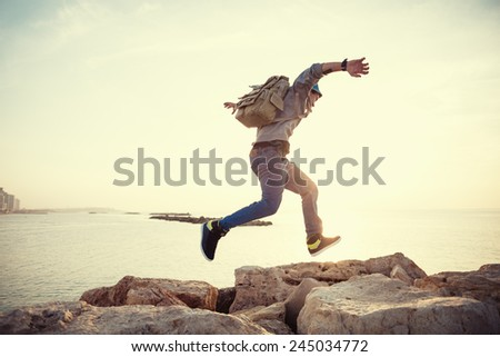 brave man with backpack running over rocks near ocean in sunset - stock photo