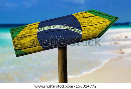 Brazil flag wooden sign with a beach on background - Latin America - stock photo