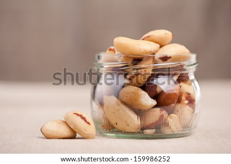 Brazil nuts from Bertholletia excelsa tree in glass jar and two nuts out of jar, healthy edible seeds food ingredient on table, blurred background, horizontal orientation, front view. - stock photo