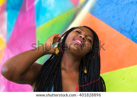 Brazilian afro woman listing to music on colorful background - stock photo