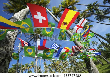Brazilian and international flags bunting decoration hanging in tropical palm grove forest Nordeste Brazil - stock photo