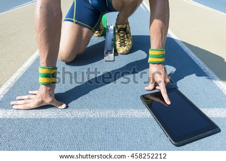 Brazilian athlete crouching at the starting line of a running track wearing Brazil colors wristbands using his tablet