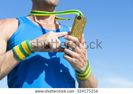 Brazilian athlete with green and yellow wristbands using gold medal mobile phone against blue sky - stock photo