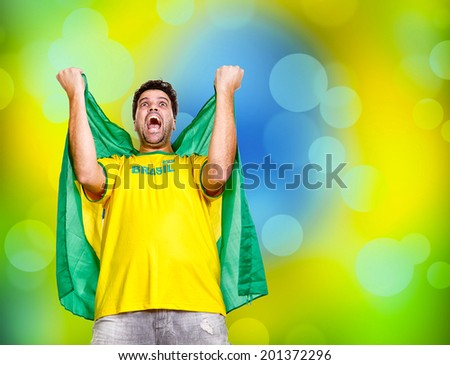Brazilian fan celebrating with Brazil flag. - stock photo