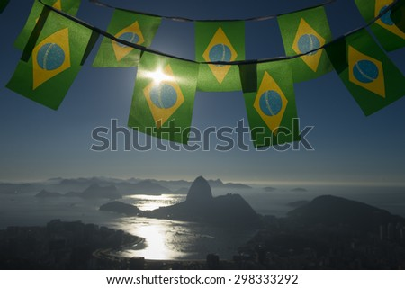 Brazilian flag bunting hanging above the city sunrise skyline view of Sugarloaf Mountain and Guanabara Bay - stock photo