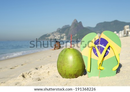 Brazilian flag flip flops sandals stuck in the sand with green coconut on Ipanema Beach against a backdrop of Two Brothers Dois Irmaos Mountain Rio de Janeiro Brazil - stock photo