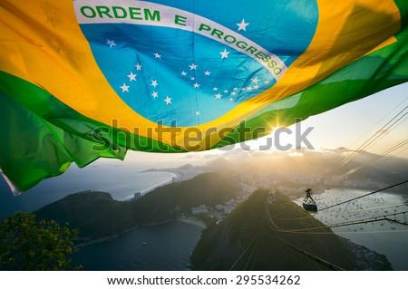 Brazilian flag shines above the golden sunset city skyline at Sugarloaf Pao de Acucar Mountain in Rio de Janeiro Brazil - stock photo