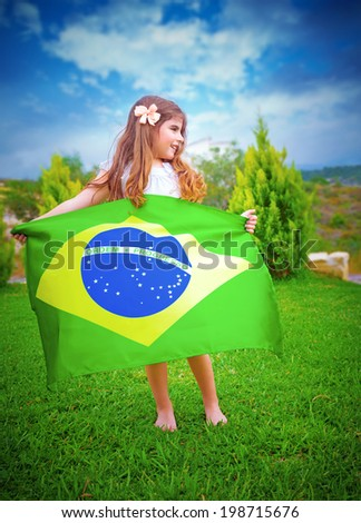 Brazilian football team fan, attractive little girl holding in hands big Brazil national flag, playing outdoors, enjoying football competition - stock photo