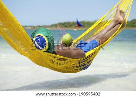 Brazilian man relaxing in beach hammock drinking fresh coconut water coco verde gelado - stock photo