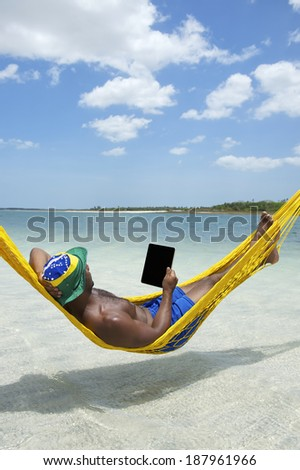 Brazilian man using tablet computer relaxing in hammock on beach over the sea - stock photo