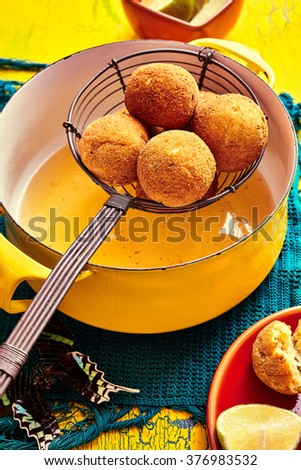 Brazilian national dish of bolhinos in frying basket over pot of oil on blue table cloth and yellow table - stock photo