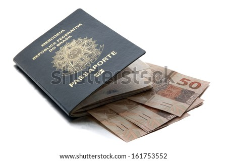 Brazilian passport and currency (Real) / A passport is a government-issued document that certifies the identity and nationality of its holder for the purpose of international travel. - stock photo